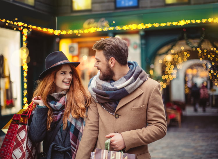 Young couple walking in front of Christmas store windows. Holding shopping bags. Wearing warm clothes, hats and scarves. Vienna, Austria. Smiling and talking.