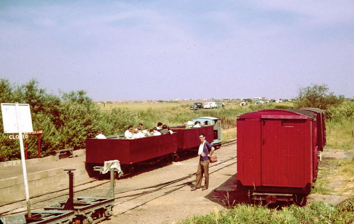 "It's a sunny June day in 1961 and the LCLR has been open for less than a year but is developing rapidly. A train of two open carriages converted from First World War Class D bogie wagons is ready to depart for the Beach, behind the line's first loco, Motor Rail 'Simplex' ""Paul"" (builder's number 3995 of 1926). On the right are former WW1 ambulance vans which once carried potatoes on the Nocton Estates Railway"