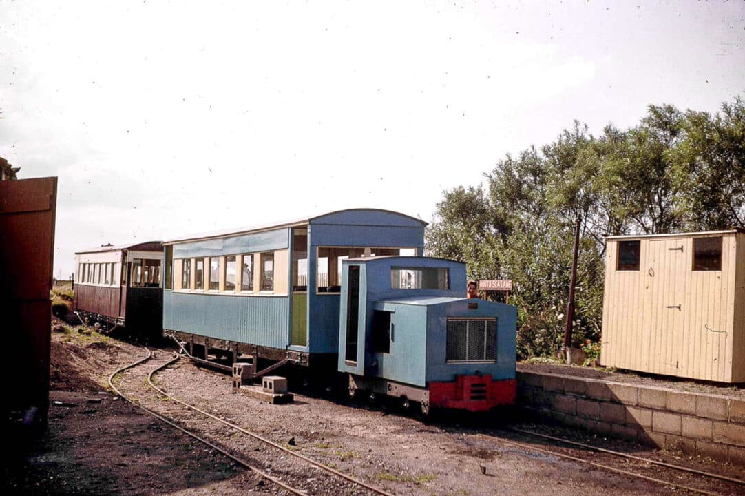 "back to 1962 and it's the original North Sea Lane station, where recently acquired and re-bodied 'Simplex' ""Wilton"" (builder's number 7481 of 1940) is ready to depart for Beach with one of the former Ashover Light Railway carriages restored by the LCLR after years as a sports pavilion at Clay Cross, Derbyshire"
