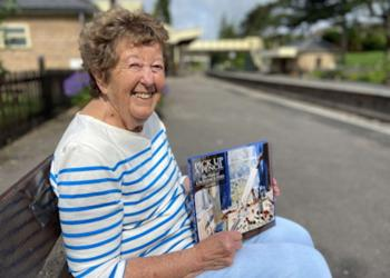 Jean Bray at Winchcombe station with her lavish book about the life and work of her late husband Laurence Fish